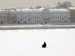 A fisherman in the middle of the frozen Neva river in winter