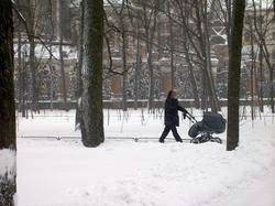 A mother walking with a baby carriage in a St. Petersburg park