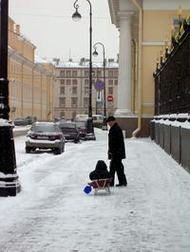 A father pulling sledge with his son